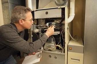 Service technician inspecting furnace
